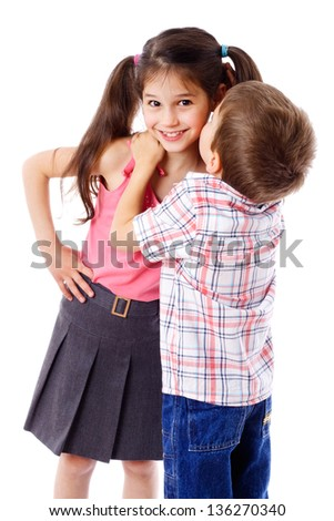 Little boy whispering something to smiling girl, isolated on white - stock photo