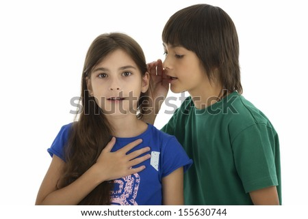 Little boy whispering something to surprised girl, isolated on white