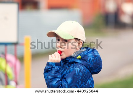 little boy whistles in a whistle at a playground - stock photo