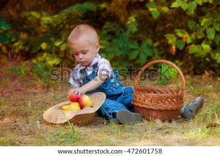 Little boy with a basket of apples and pears in autumn garden