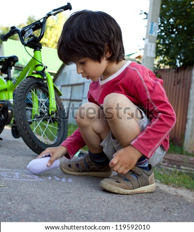 little boy with a bicycle drawing with chalk on asphalt - stock photo
