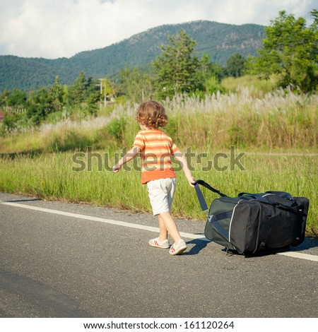little boy with a big bag walking down the road in the day time - stock photo