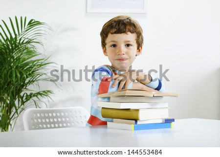 Little boy with a books looking at camera./ Schoolboy studying in home. - stock photo