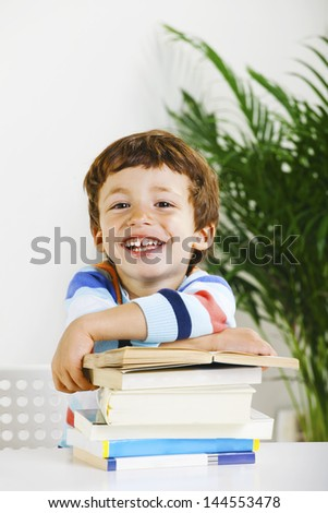 Little boy with a books looking at camera./ Smiling schoolboy studying in home. - stock photo