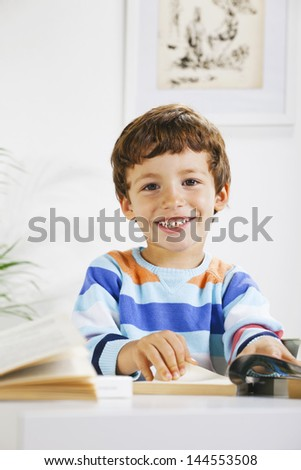 Little boy with a books looking at camera./ Smiling schoolboy studying in home.