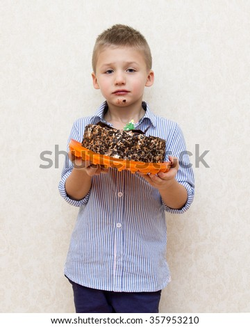 Little boy with a cake , his face is smeared with chocolate - stock photo