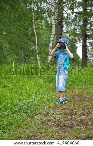 Little boy with a camera shooting outdoor. Kid taking a photo using a digital cam. Green summer  forest glade. Photographing. Happy childhood.
