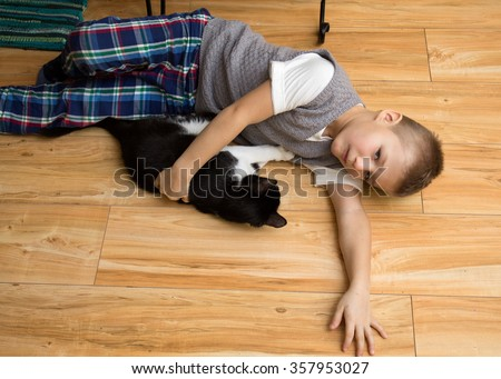 Little boy with a cat are laying on the floor together