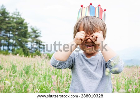 little boy with a crown  with binocular hands - stock photo