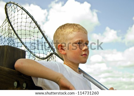 Little boy with a fishing net is leaning on a wooden dock railing