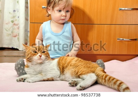 Little boy with a ginger cat sitting on a pink blanket. - stock photo