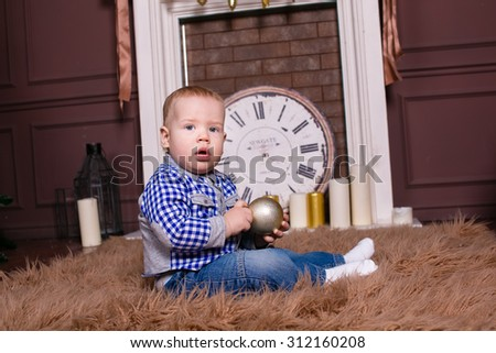 Little boy with a golden Christmas tree ball in hands sitting on the furs by the fire, New Year, Christmas, holiday