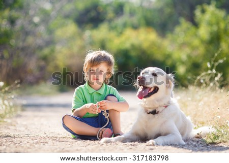 Little boy with a golden retriever dogs outdoor. Boy with a dog on the nature. child with dog outdoor. child and animal - stock photo