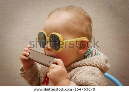 Little boy with a harmonica - stock photo