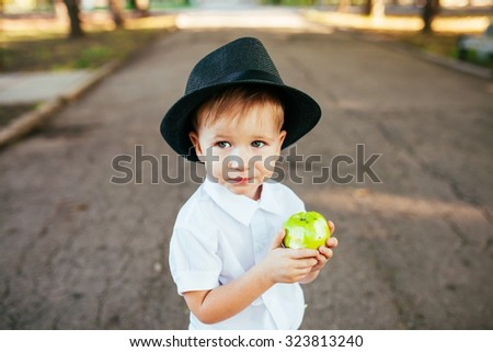 Little boy with a hat on his head in the park eating an apple - stock photo