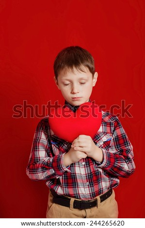 Little boy with a heart of toy in hands - stock photo