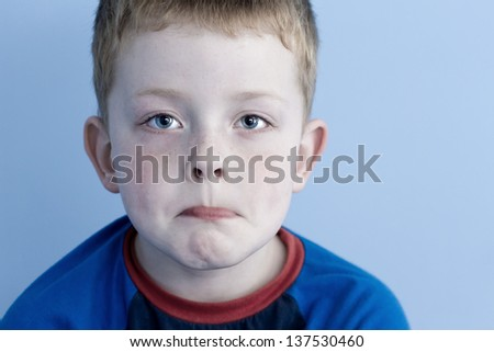 little boy with a look of sadness upon his face - stock photo