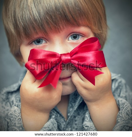 little boy with a red bow in hand - stock photo