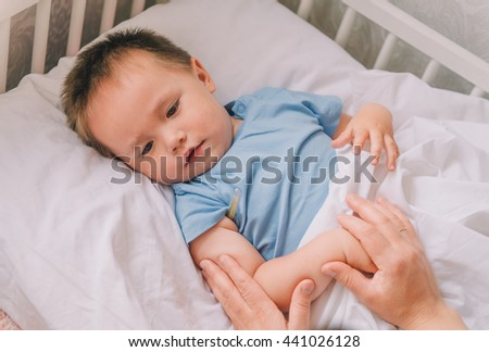 little boy with a thermometer. little boy in the bed. the boy is sick. child measure temperature. - stock photo