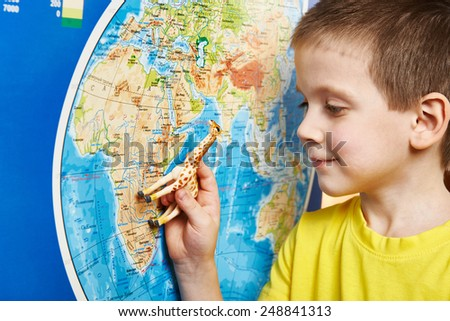 Little boy with a toy giraffe shows Africa on the world map