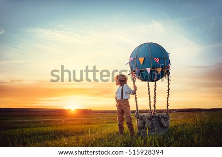 Little boy with aerostat at sunset