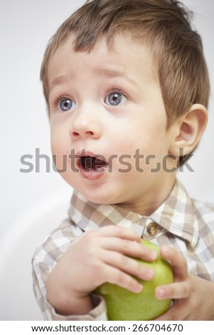 Little boy with an apple looking surprised - stock photo