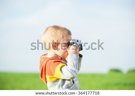 Little boy with an old camera shooting outdoor. - stock photo