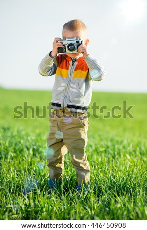 Little boy with an old camera shooting outdoor. Kid taking a photo using a vintage retro film cam. Green summer field. - stock photo