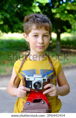 Little boy with an old camera. Young Photographer. Child with retro camera. Cheerful smiling kid holding a vintage camera, ready to make a picture. Bright summer fun photo in the park. - stock photo