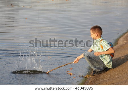 little boy with backpack near pond. he is wallop water. splash. - stock photo