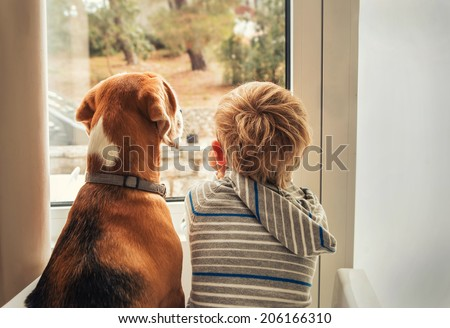 little boy with best friend looking through window - stock photo
