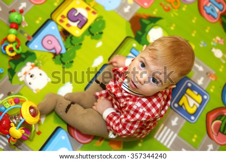 Little boy with big blue eyes sitting on a colorful children's warm rug and play with bright toys - stock photo