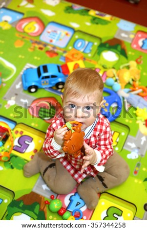 Little boy with big blue eyes sitting on a colorful children's warm rug and play with bright toys