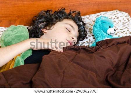 Little boy with black hair sleeping with his blue teddy bear and green turtle covered with a brown comforter.