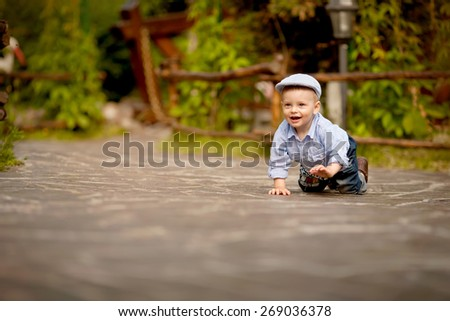 little boy with blue skirt and blue cap is crawling on the road in the park - stock photo