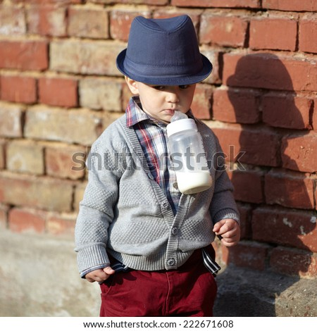 little boy with bottle in mouth - stock photo