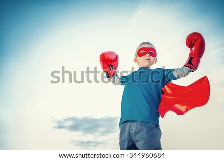 Little boy with boxing gloves outdoors - stock photo