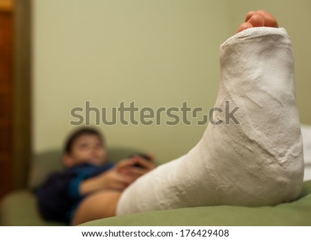 Little boy with broken leg in plaster cast lying on sofa at home and using smart phone. Focus in foreground - stock photo