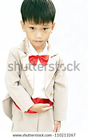 Little boy with brown tuxedo and red bow tie on white background