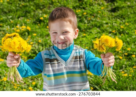 Little boy with bunch of dandelions on green field - stock photo