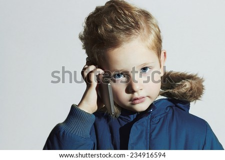 little boy with cellphone. modern child in winter coat. fashion kids.children - stock photo