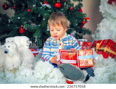 Little boy with Christmas present near decorated fir tree - stock photo