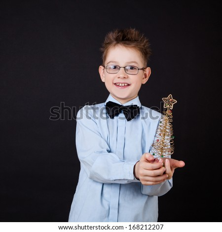 Little boy with Christmas tree over the black
