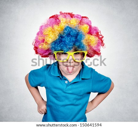 Little boy with clown wig mocking isolated on gray background  - stock photo