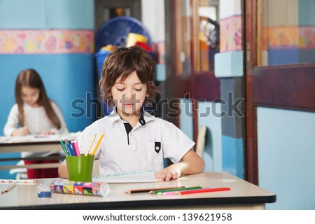Little boy with color pencils and drawing paper while girl in background at kindergarten