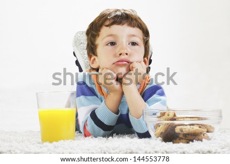 Little boy with cookies and orange juice stretching on carpet./ Angry child with breakfast in home. - stock photo