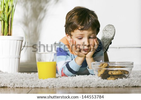 Little boy with cookies and orange juice stretching on carpet./ Child with diabetes looking cookies. - stock photo