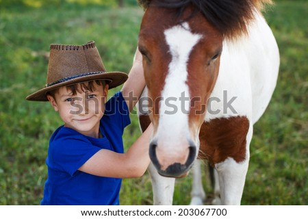Little boy with cowboy hat and pony horse, friends - stock photo