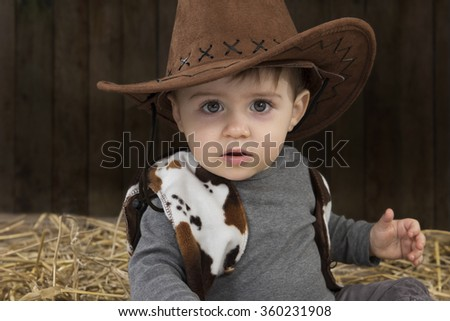 Little boy with cowboy hat in a barn - stock photo