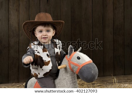 Little boy with cowboy hat on toy horse in a barn